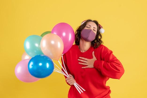 Jovem mulher segurando balões na máscara em amarelo de frente