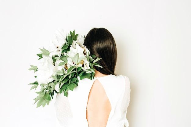 Jovem mulher segurando buquê de peônias brancas em fundo branco