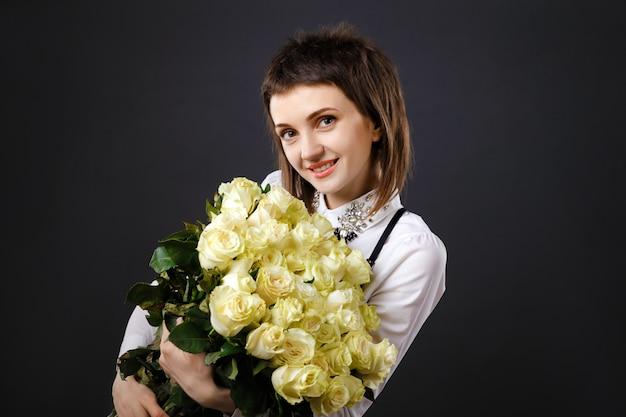 Jovem mulher segurando buquê de rosas brancas
