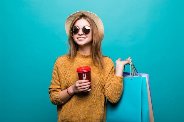 Jovem mulher segurando café para ir e sacolas de compras enquanto sorrindo na parede azul
