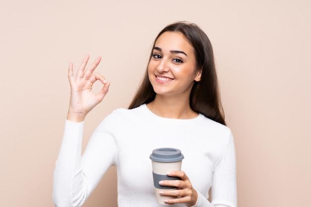 Jovem mulher segurando café para levar embora fazendo sinal de ok