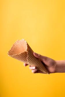 Jovem mulher segurando casquinha de sorvete - fundo amarelo