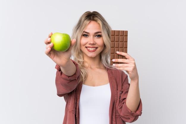 Jovem mulher segurando chocolate e uma maçã
