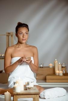 Jovem mulher segurando coco, relaxante no salão spa.