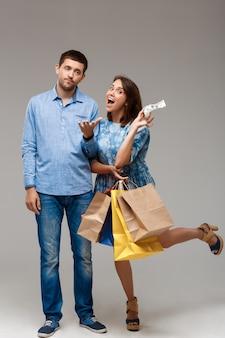 Jovem mulher segurando compras, tendo último dinheiro do homem