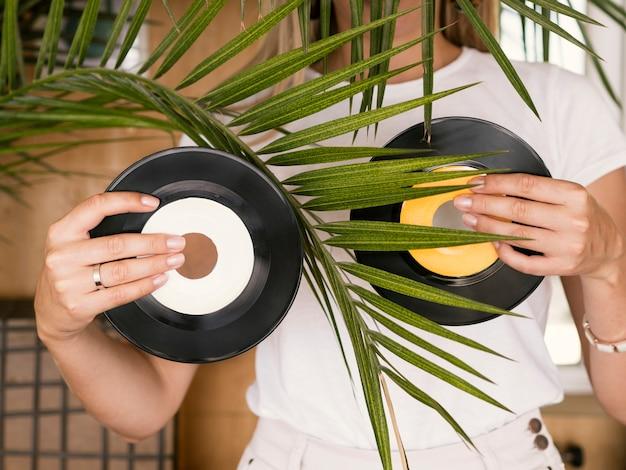 Jovem mulher segurando discos de vinil nas duas mãos atrás da planta