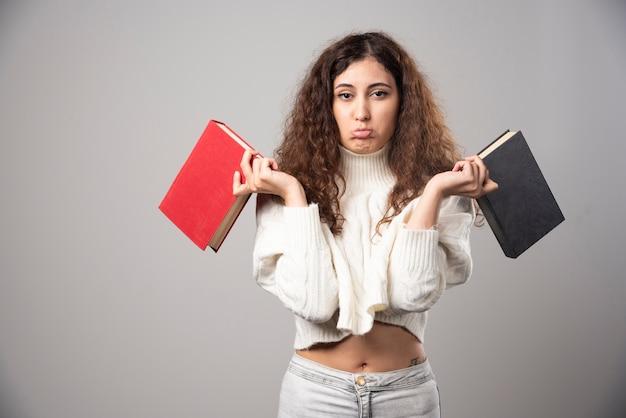 Jovem mulher segurando dois livros em uma parede cinza. foto de alta qualidade