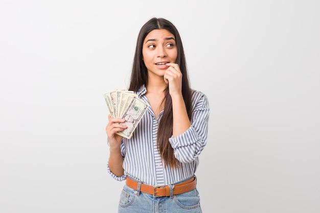 Jovem mulher segurando dólares relaxado pensando em algo