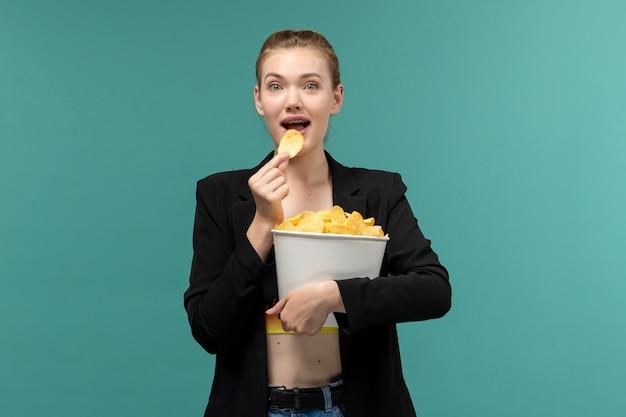 Jovem mulher segurando e comendo batatinhas de frente, assistindo filme na superfície azul
