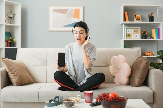 Jovem mulher segurando e olhando para o telefone, sentada no sofá atrás da mesa de centro na sala de estar