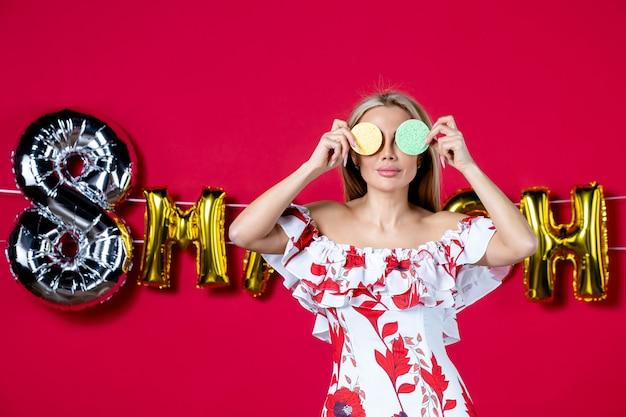 Jovem mulher segurando esponjas coloridas para a remoção de maquiagem em março decorada com glamour vermelho