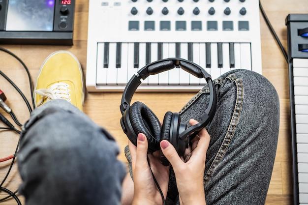 Jovem mulher segurando fones de ouvido do estúdio, ponto de vista baleado. vista superior do músico feminino em home studio com modernos instrumentos eletrônicos.