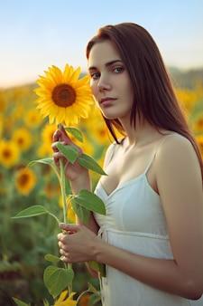 Jovem mulher segurando girassol no campo de verão