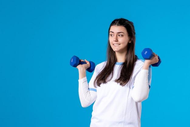 Jovem mulher segurando halteres azuis de frente