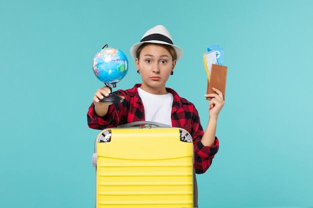 Jovem mulher segurando ingressos e um globo no espaço azul claro de frente