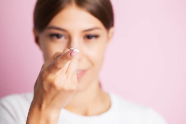 Jovem mulher segurando lentes de contato no dedo.