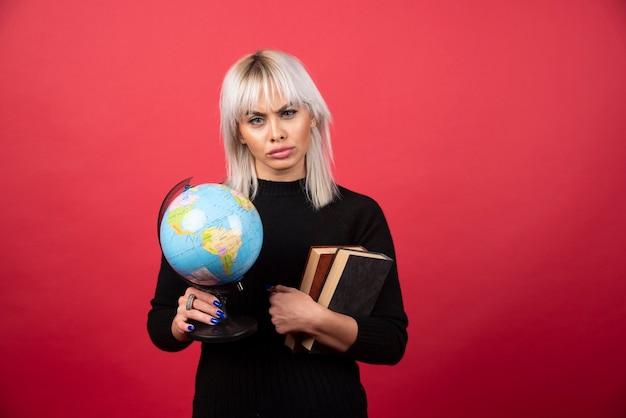 Jovem mulher segurando livros com o globo terrestre e olhando para a câmera