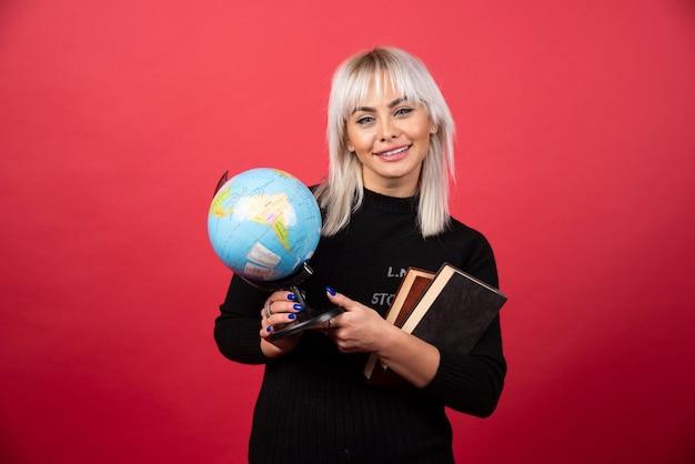 Jovem mulher segurando livros com o globo terrestre e sorrindo