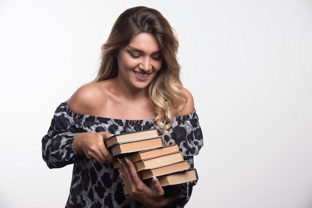 Jovem mulher segurando livros enquanto ri.