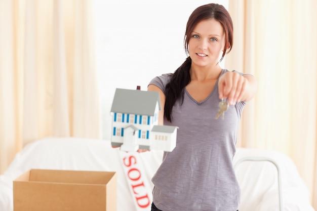 Jovem, mulher, segurando, modelo, casa, chaves
