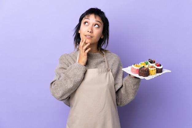 Jovem mulher segurando muitos mini bolos diferentes sobre roxo isolado, pensando uma idéia