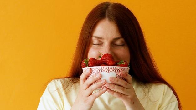 Jovem mulher segurando nas mãos e cheirando morangos suculentos grandes e frescos. sobre fundo amarelo