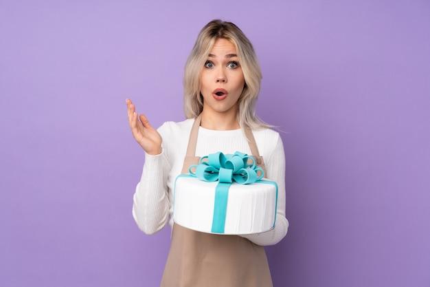 Jovem mulher segurando o bolo sobre parede isolada