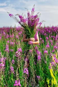 Jovem mulher segurando o buquê de flores cor de rosa.