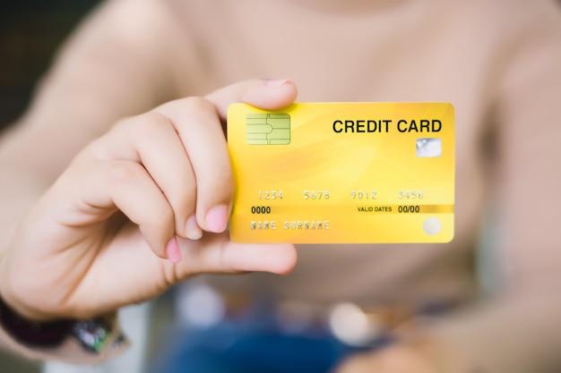 Jovem mulher segurando o cartão de crédito, compras on-line ou pagando o conceito