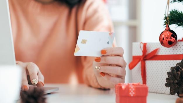 Jovem mulher segurando o cartão de crédito e fazendo compras on-line.
