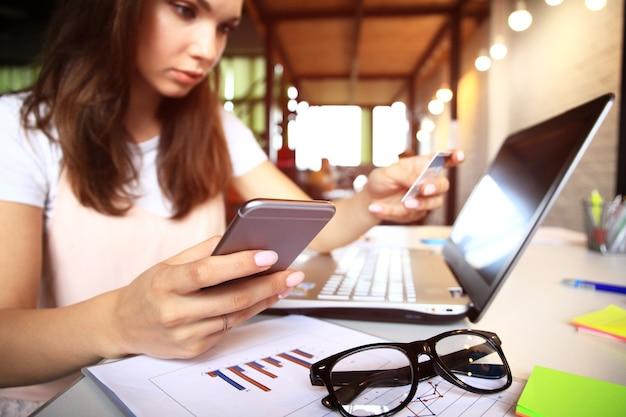 Jovem mulher segurando o cartão de crédito e usando o computador portátil. conceito de compras online.
