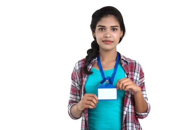 Jovem mulher segurando o cartão de identificação de plástico em branco branco de identificação.