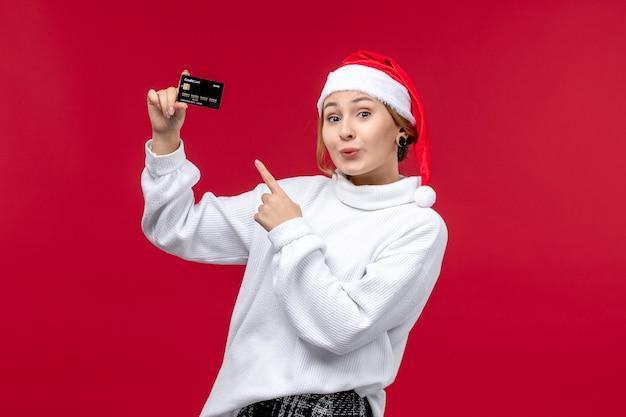 Jovem mulher segurando o cartão do banco na mesa vermelha