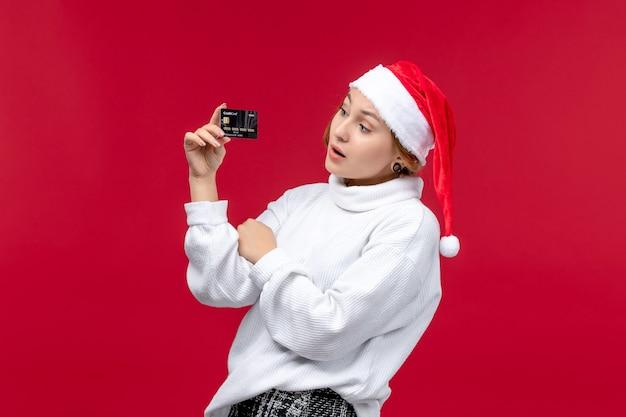 Jovem mulher segurando o cartão do banco no chão vermelho, vista frontal, natal, feriado, vermelho, dinheiro
