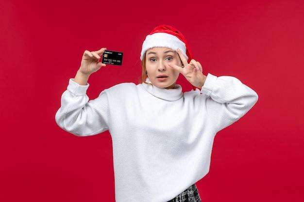 Jovem mulher segurando o cartão do banco sobre fundo vermelho.