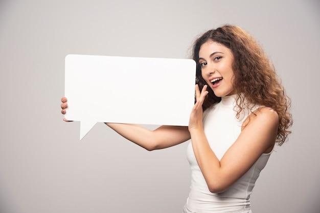 Jovem mulher segurando o cartaz de discurso branco em branco vazio. foto de alta qualidade