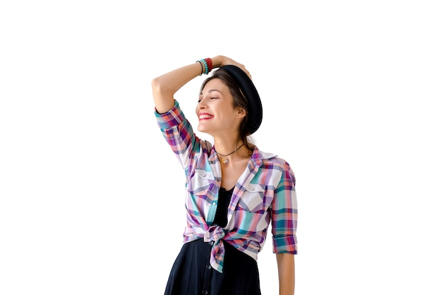 Jovem mulher segurando o chapéu com o braço direito a rir