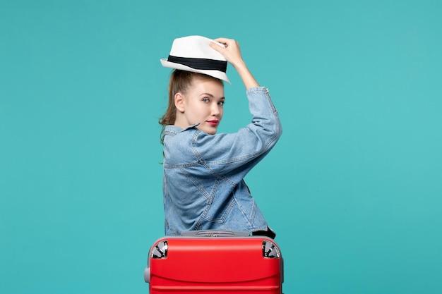Jovem mulher segurando o chapéu e se preparando para uma viagem no espaço azul