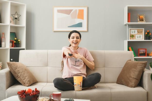 Jovem mulher segurando o controle remoto da tv para a câmera, sentada no sofá atrás da mesa de centro da sala de estar
