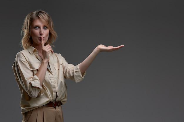 Jovem mulher segurando o dedo na boca para mantê-lo quieto, apontando para o espaço da cópia