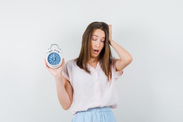 Jovem mulher segurando o despertador em t-shirt, saia e parecendo com sono. vista frontal.