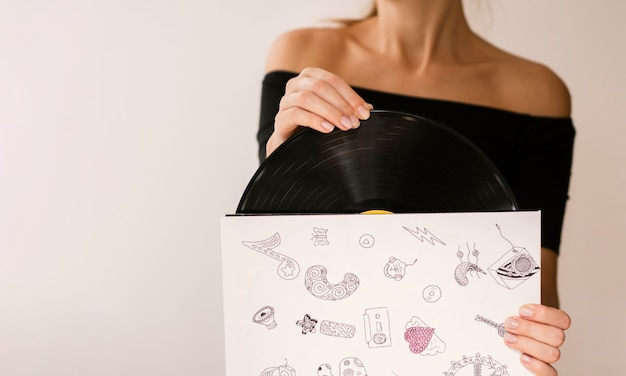 Jovem mulher segurando o disco de vinil em seu caso
