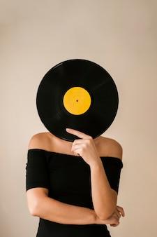 Jovem mulher segurando o disco de vinil sobre o rosto
