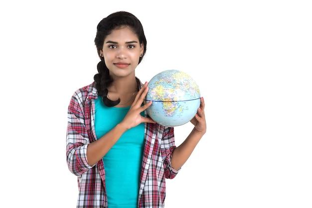Jovem mulher segurando o globo do mundo e posando em um fundo branco.
