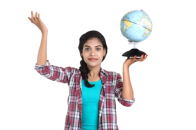 Jovem mulher segurando o globo do mundo e posando.