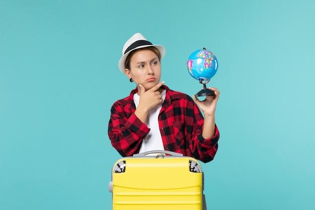 Jovem mulher segurando o globo e se preparando para uma viagem no espaço azul.