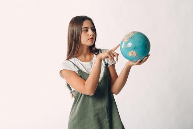 Jovem mulher segurando o globo nas mãos e apontando o dedo. conceito de turismo e viagens.