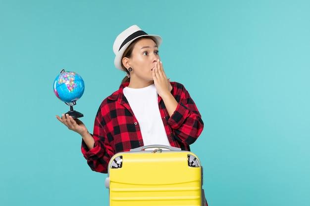 Jovem mulher segurando o globo no espaço azul claro de frente
