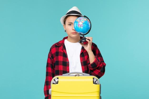 Jovem mulher segurando o globo no espaço azul de frente