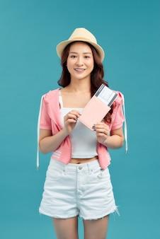 Jovem mulher segurando o passaporte, cartão de crédito. viajante de garota sorridente sobre fundo azul.